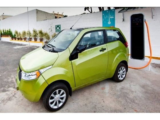 Mahindra Reva e2o electric car hooked to a charging station